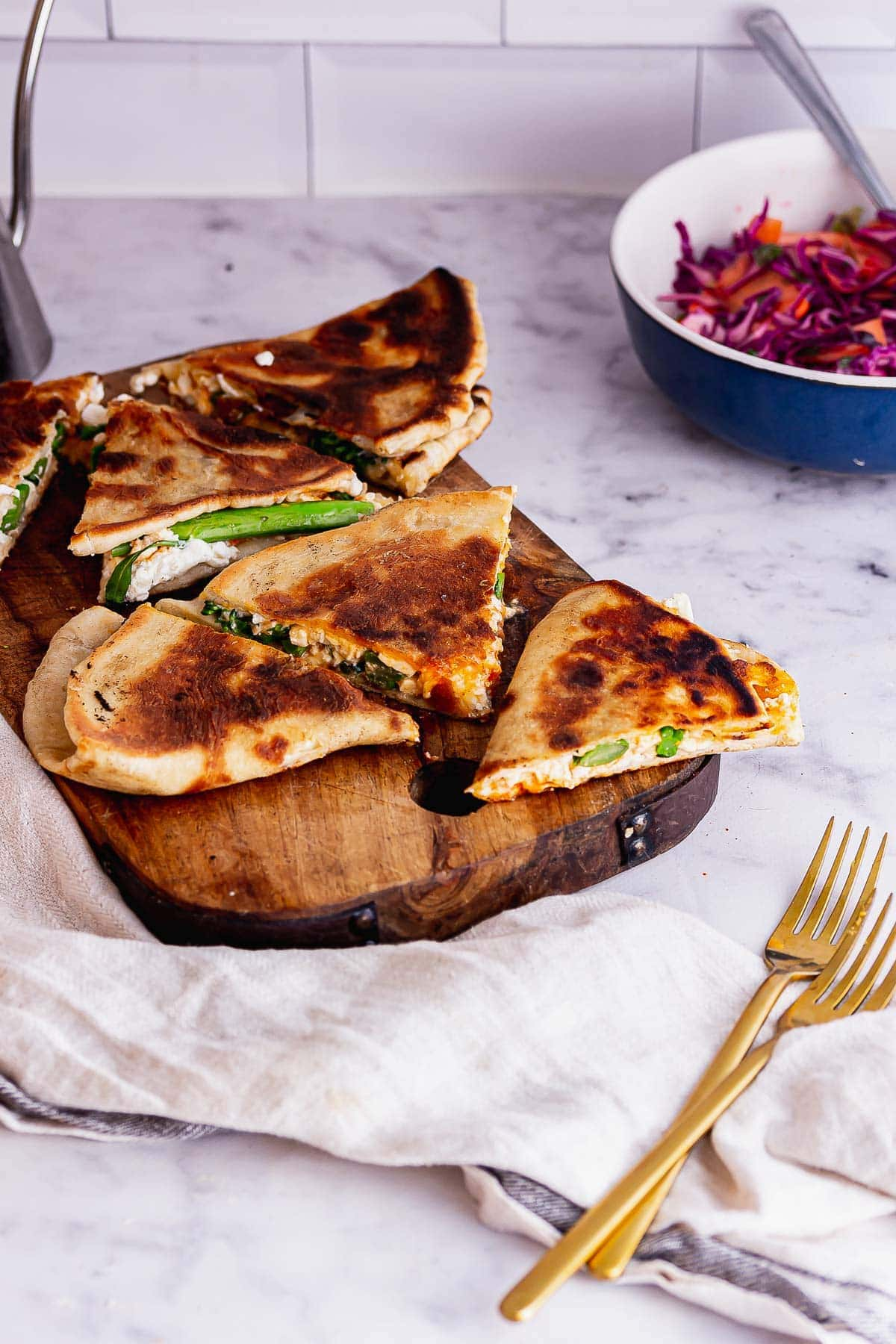 Feta flatbreads on a chopping board with a cloth and gold forks
