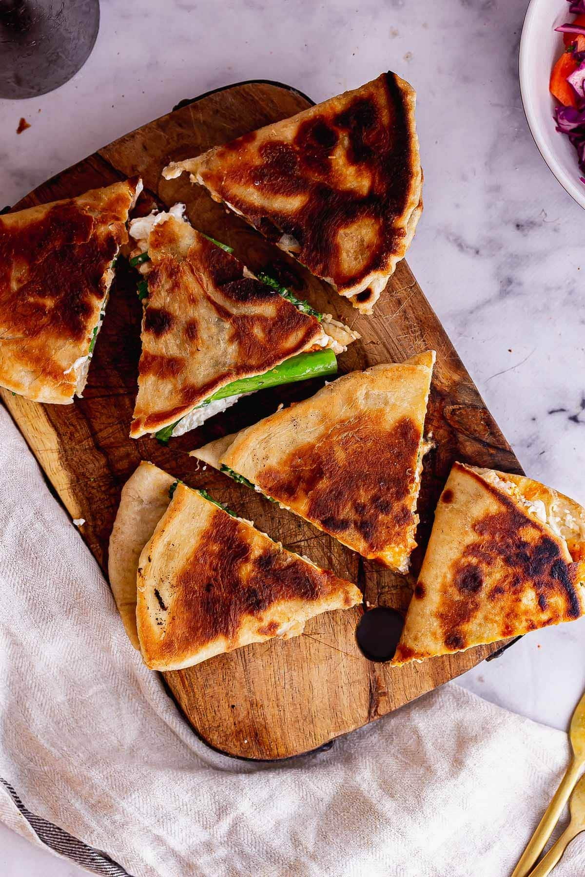 Overhead shot of folded flatbread sandwiches on a marble background