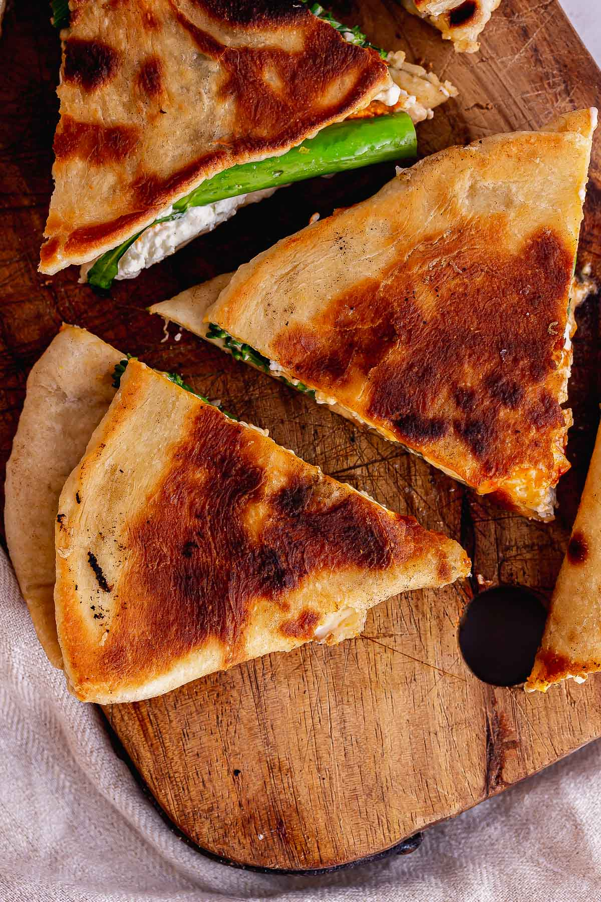 Overhead shot of flatbread triangles on a wooden board