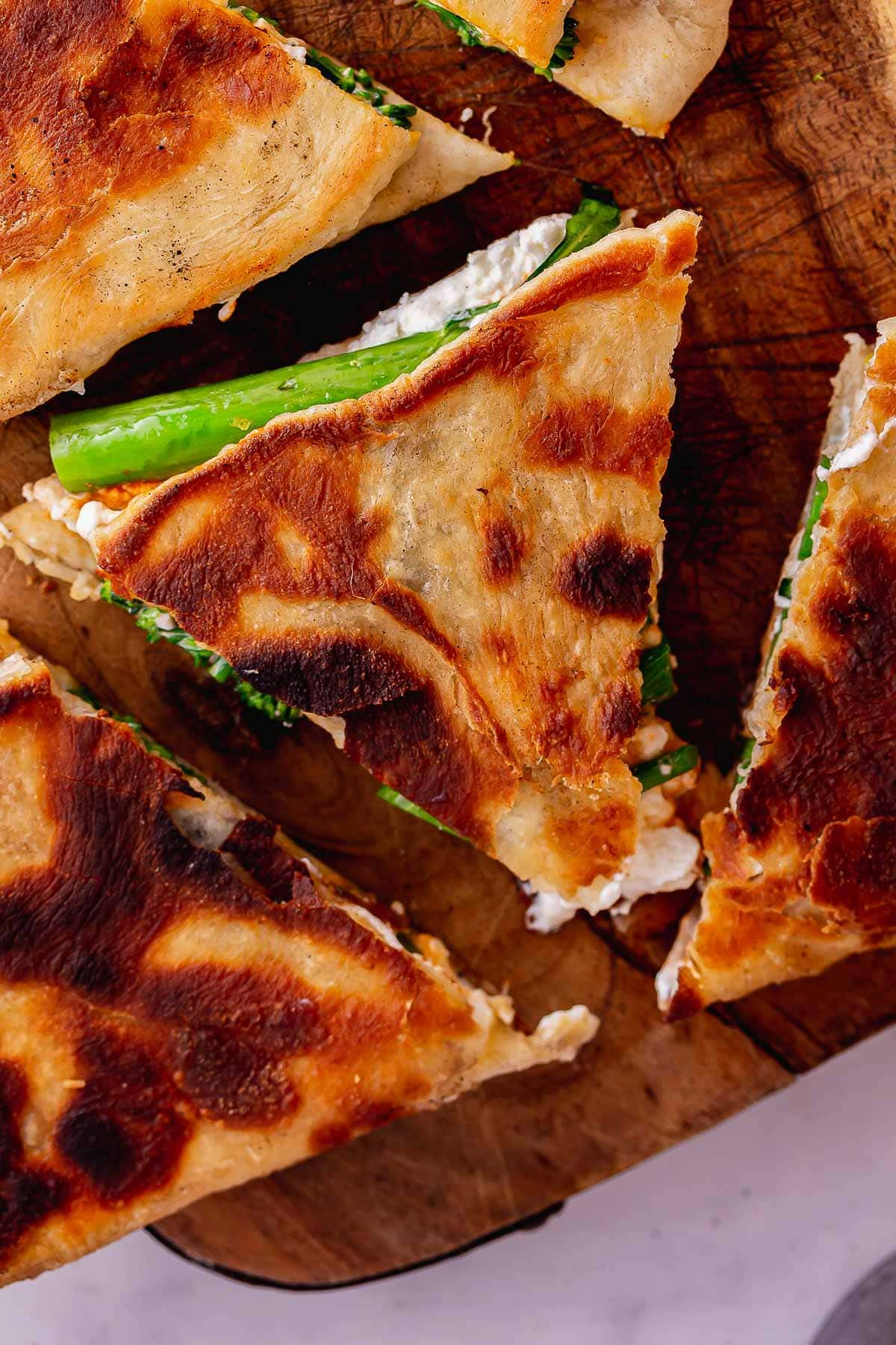Close up of cheese broccoli flatbreads on a wooden board