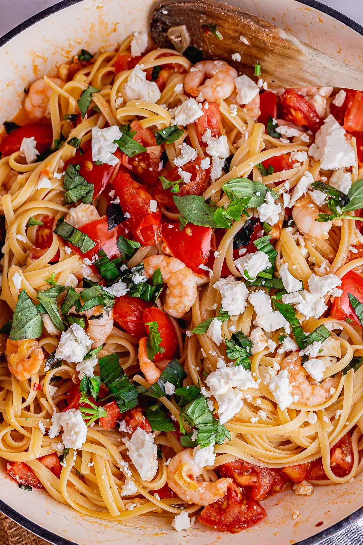 Overhead shot of prawn and feta pasta with a wooden spoon