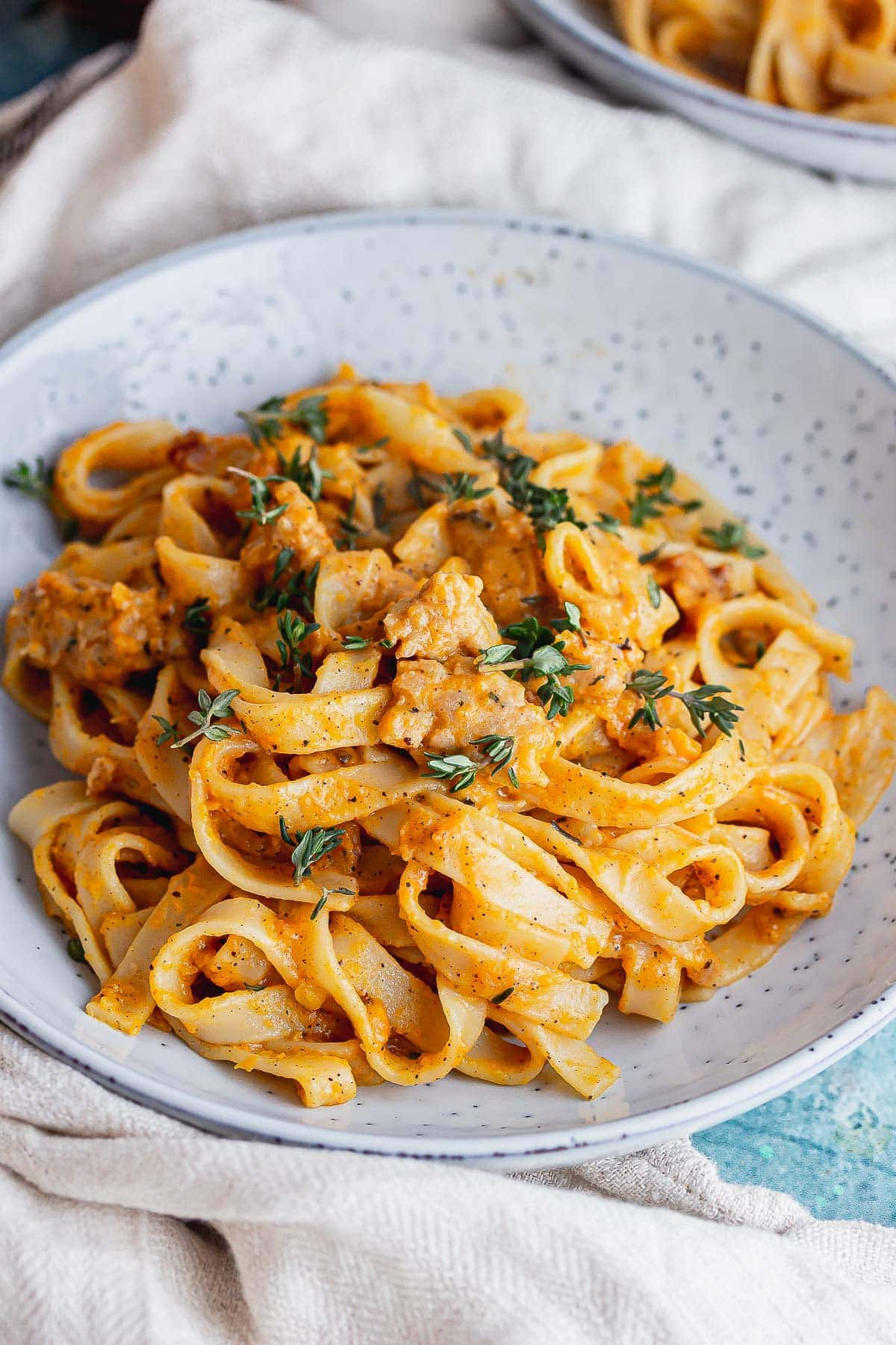 Blue bowl of squash pasta with a beige cloth