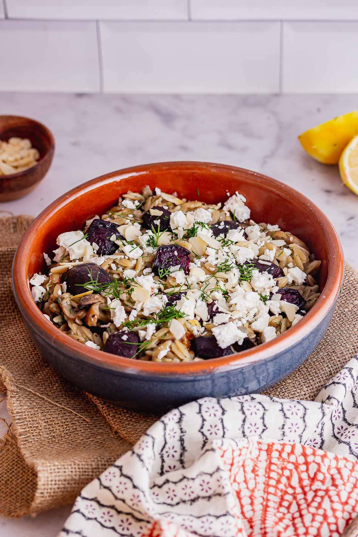 Blue bowl of mushroom orzo with feta on a marble surface