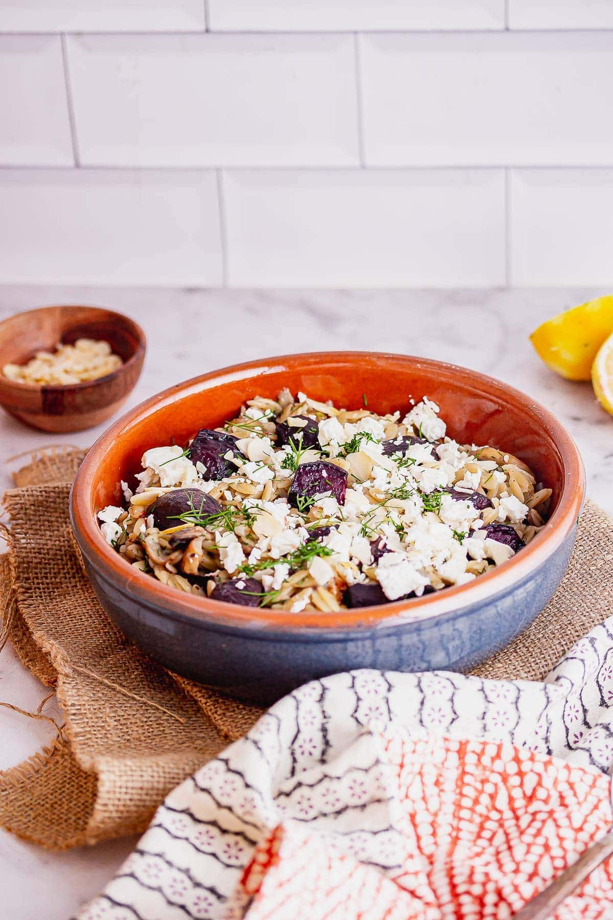 Blue bowl of mushroom orzo with a patterned towel