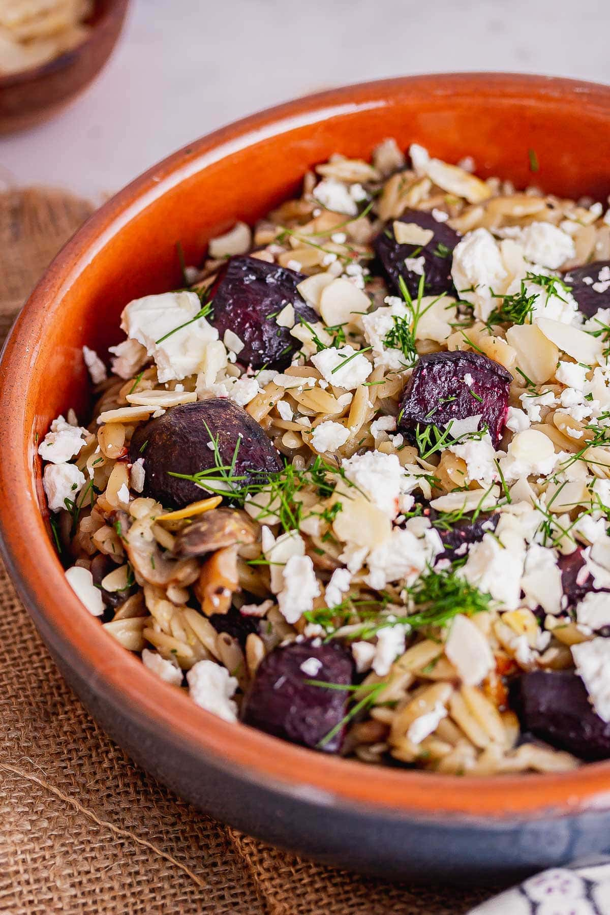 Close up of mushroom and beetroot orzo in a blue and terracotta bowl