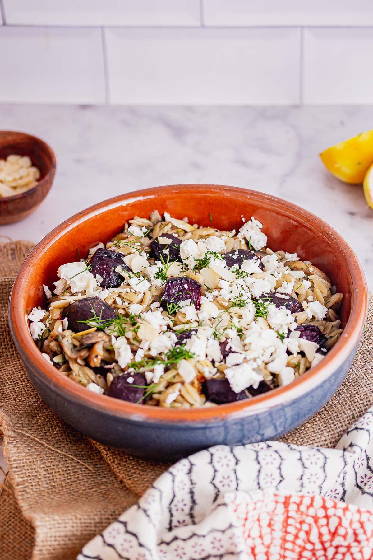 Bowl of orzo with vegetables and feta on a hessian mat