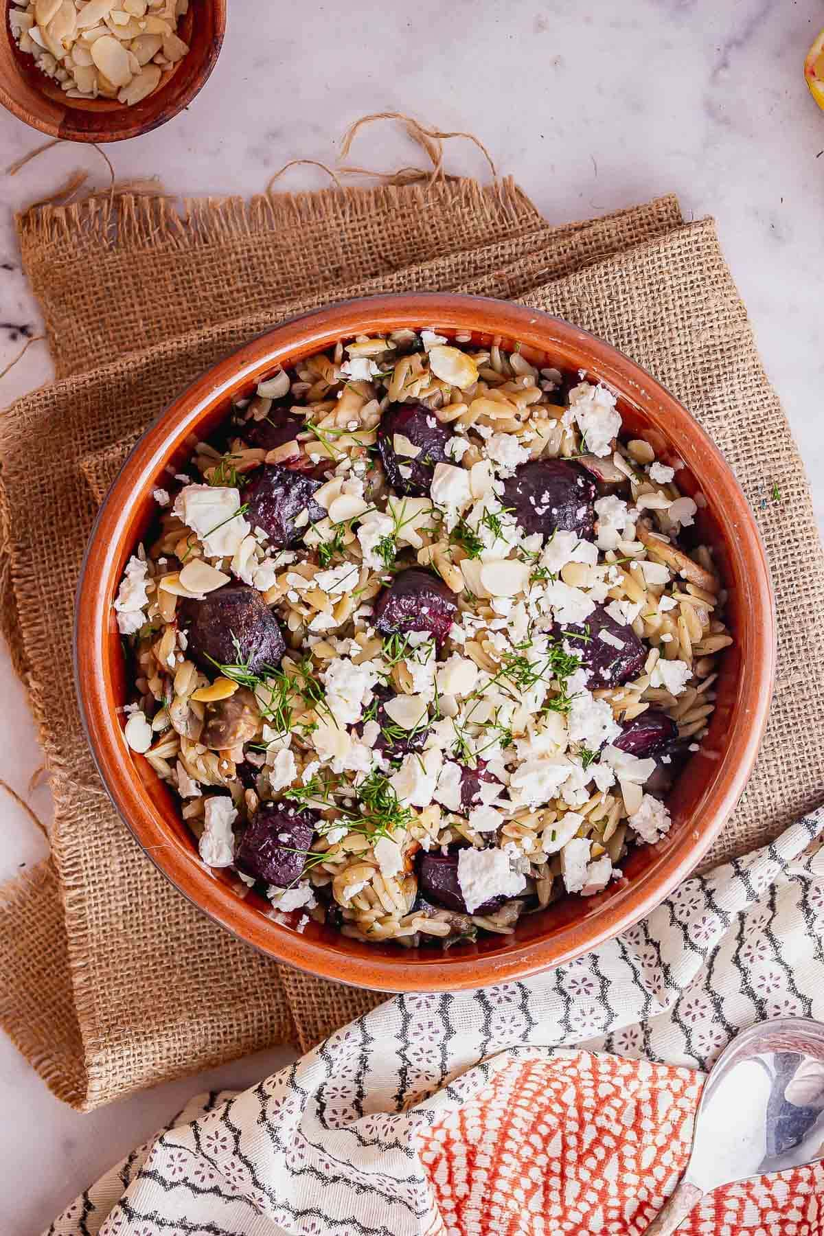Overhead shot of terracotta bowl of orzo with beetroot and feta
