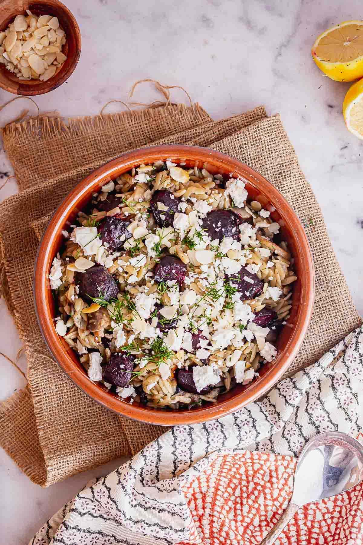 Overhead shot of a bowl of orzo on a hessian mat on a marble background
