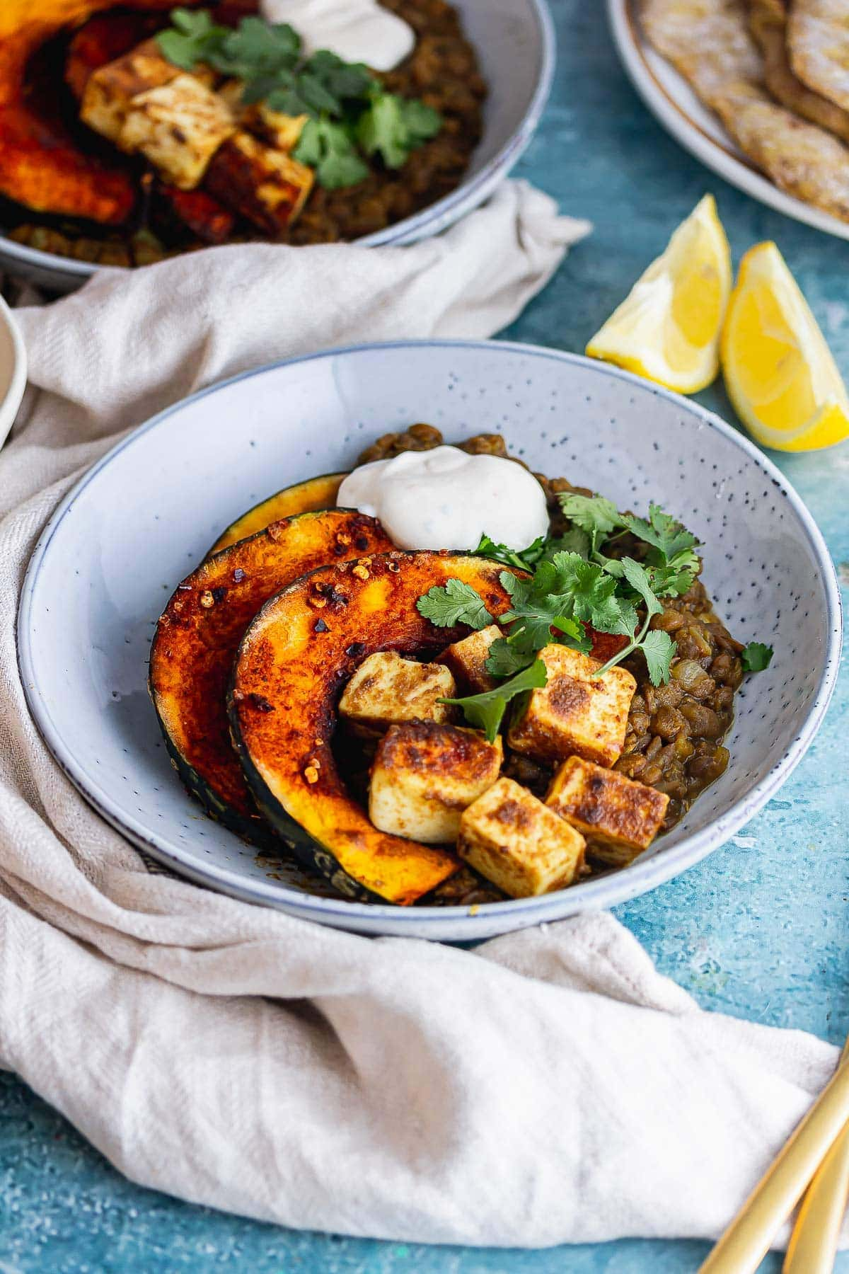Blue bowl of spicy lentils with paneer and squash on a blue background