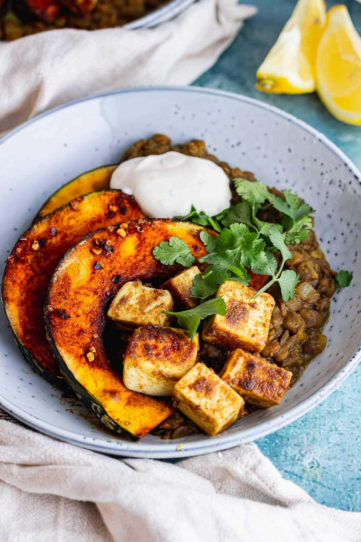 Blue bowl of lentils topped with caramelised squash with a cloth