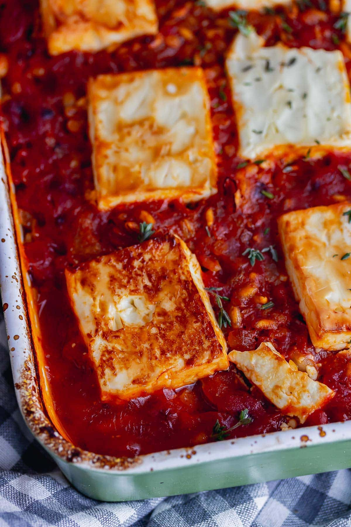 Close up of browned feta on a tomato sauce