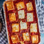 Overhead shot of tomato and feta bake on a checked cloth