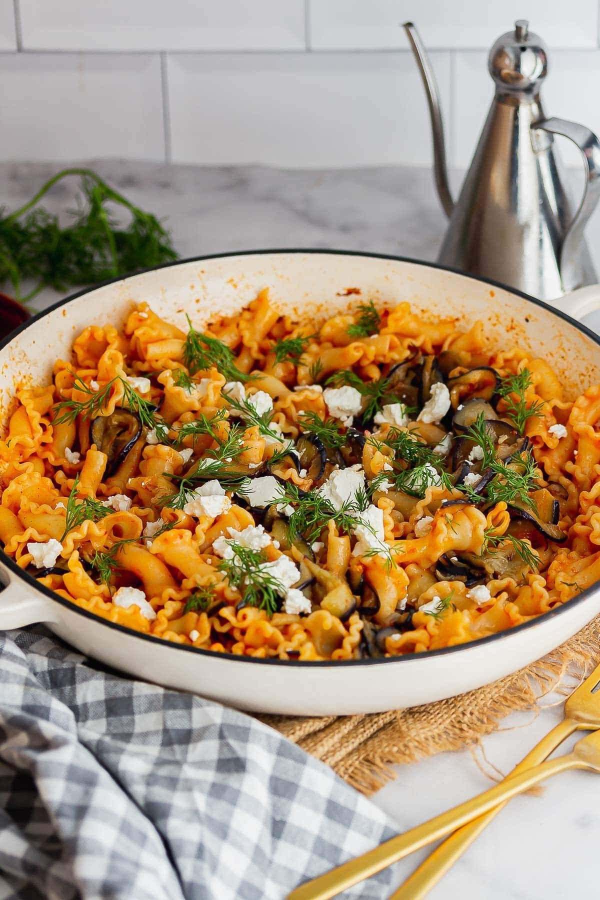White skillet of spicy pasta with aubergine on a marble surface