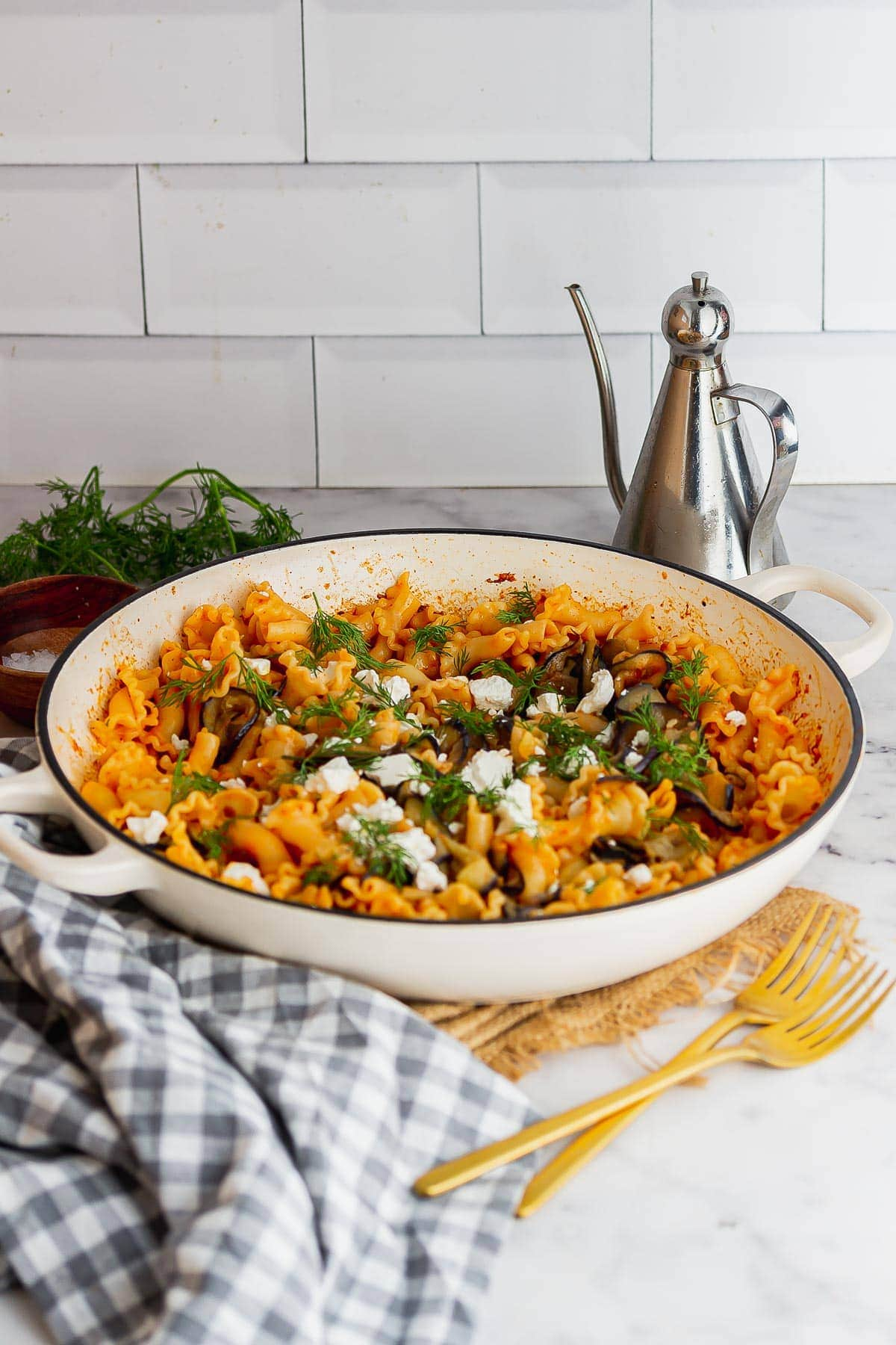 Skillet of pasta topped with feta with a checked cloth in front of a white tile background