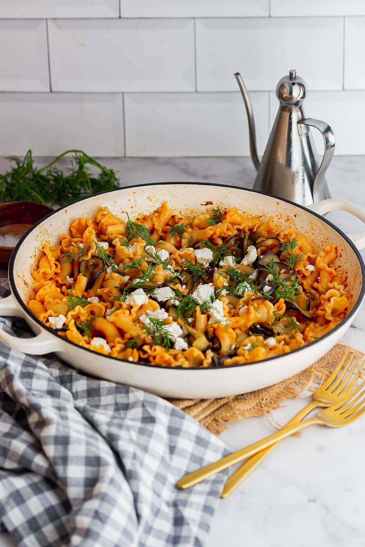 White pot of harissa eggplant pasta on a marble background