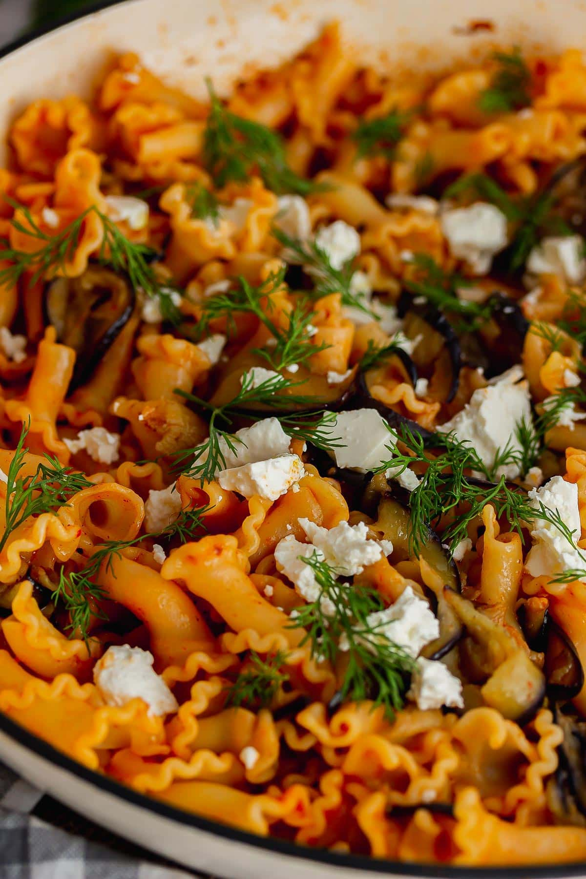 Close up of aubergine and pasta topped with feta and dill