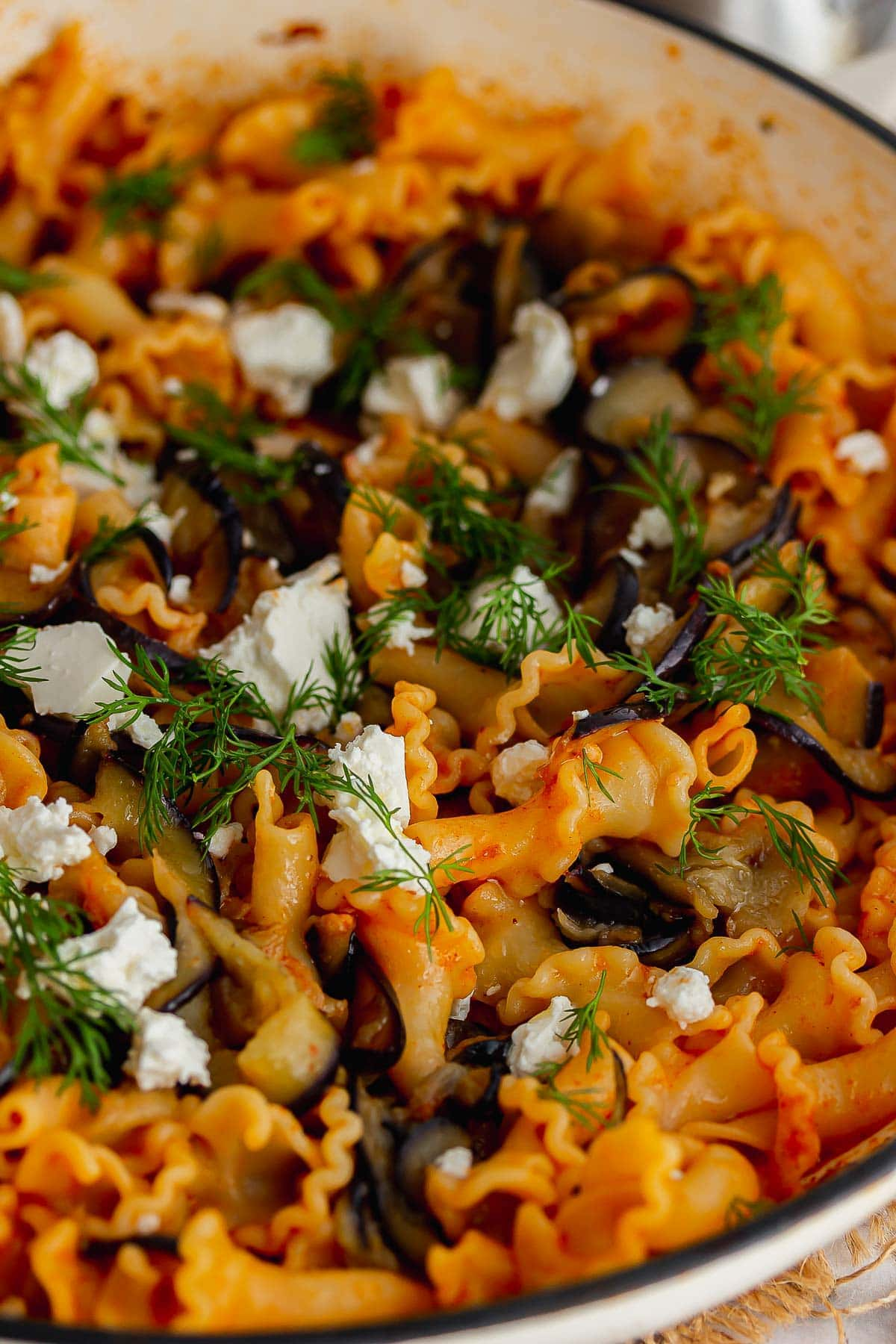 Close up of spicy aubergine pasta with feta and dill