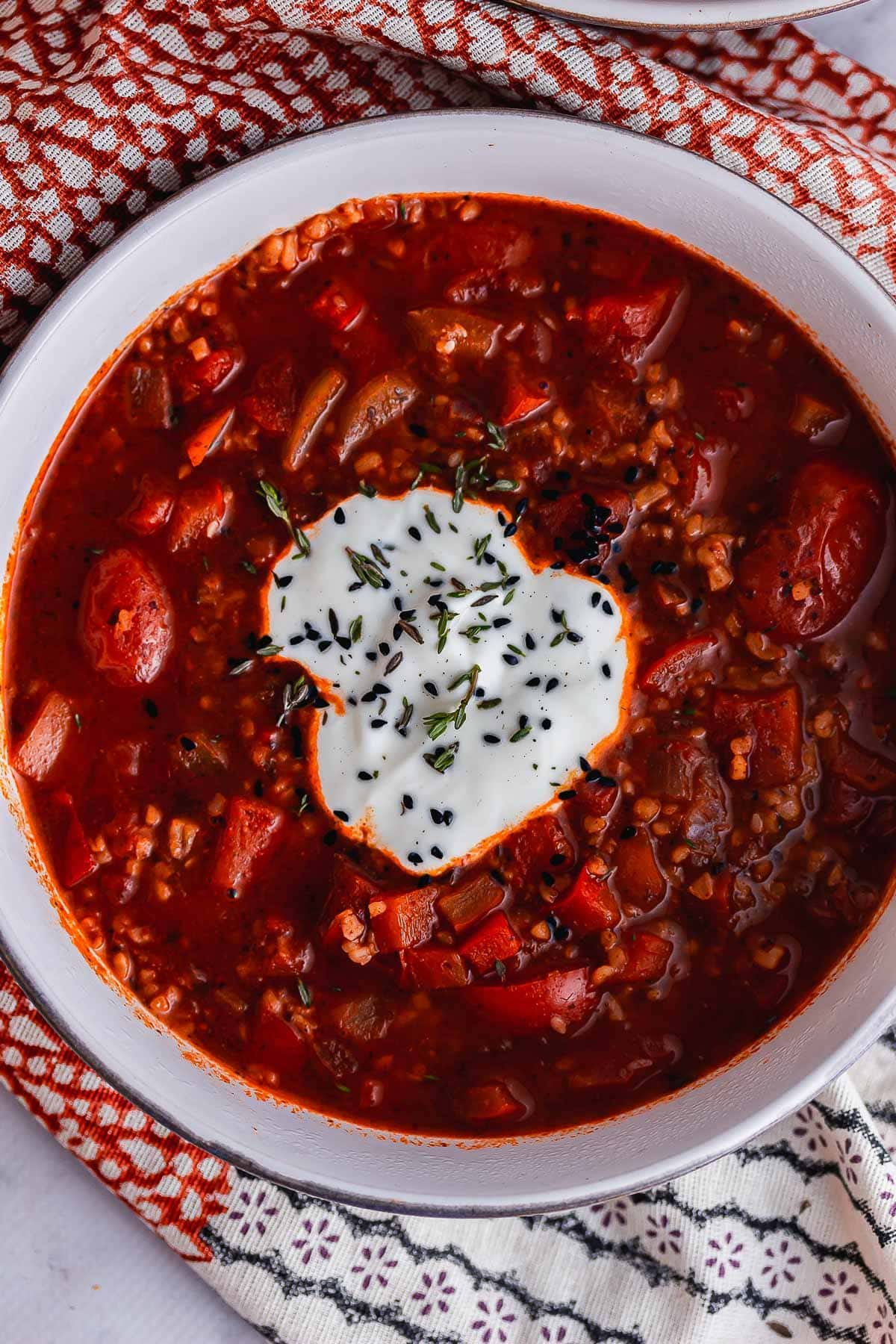 Overhead shot of spiced soup with tomato topped with yoghurt