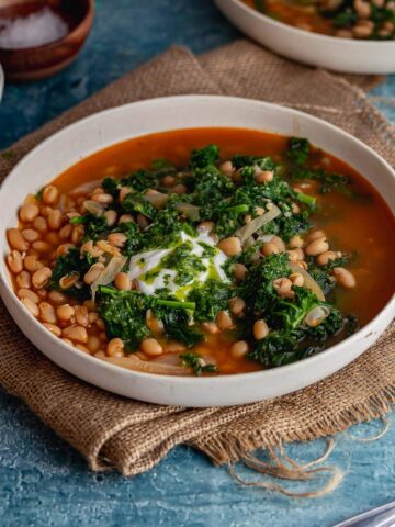White bowl of spicy soup with beans and kale on a blue background