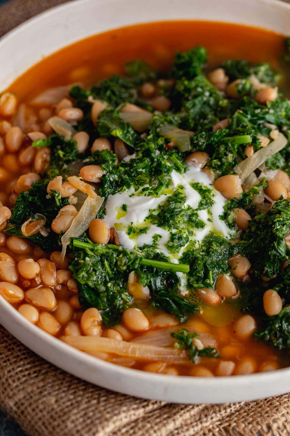 Close up of spicy bean soup with kale topped with yoghurt