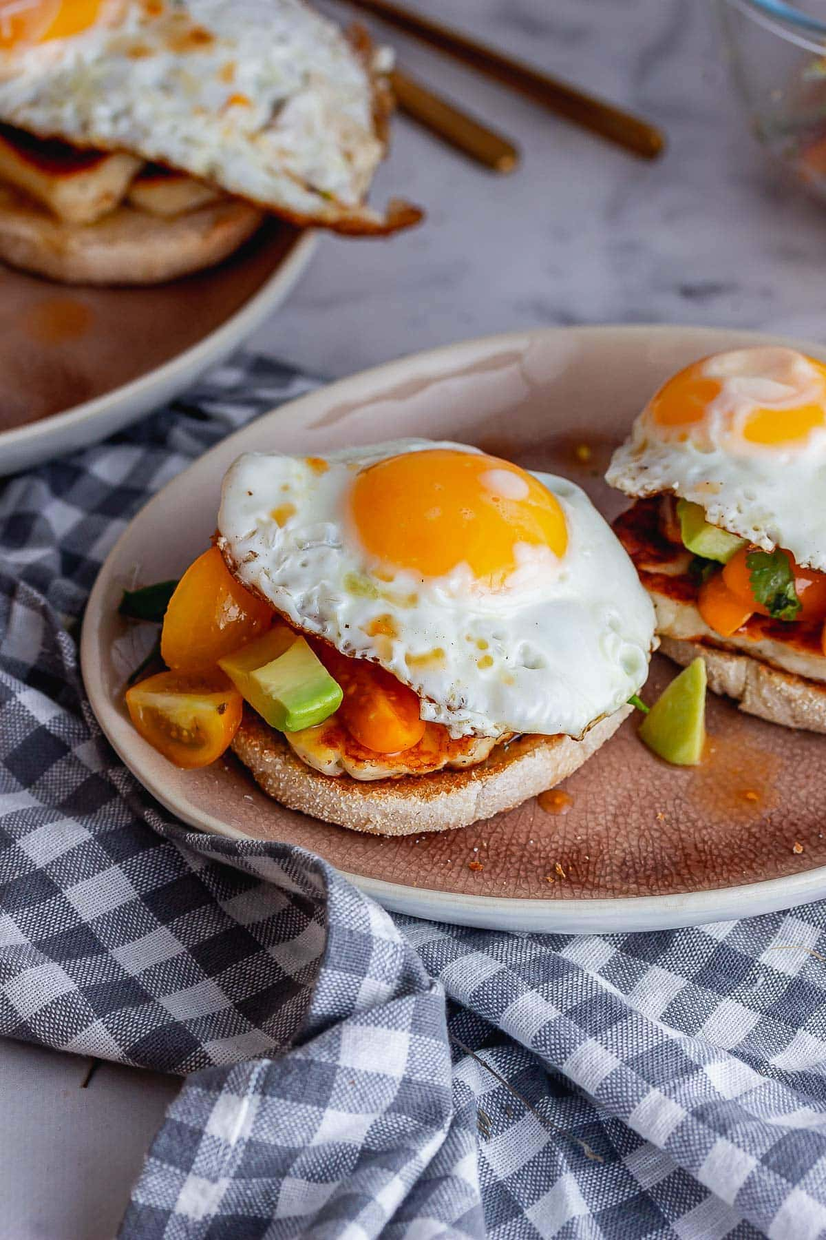 Pink plate of breakfast muffins topped with fried eggs