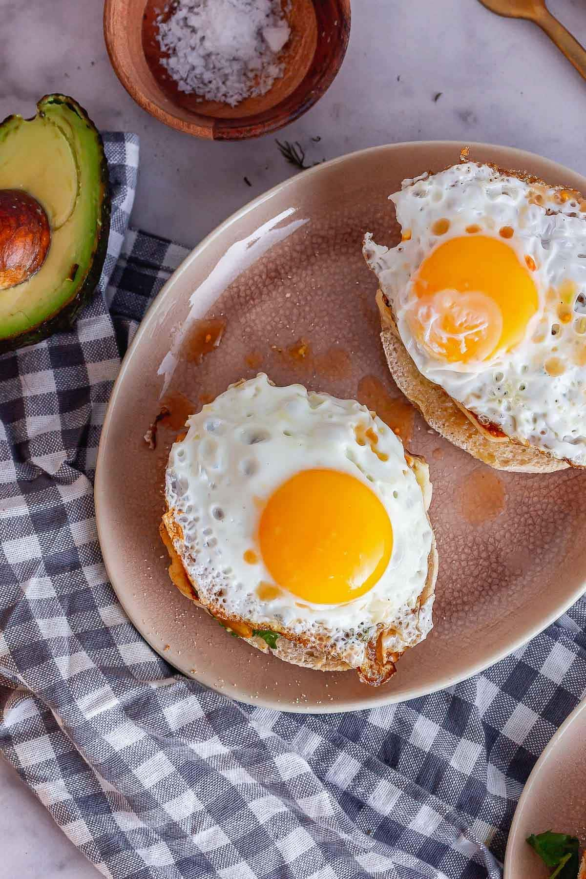 Overhead shot of fried eggs on muffins with avocado