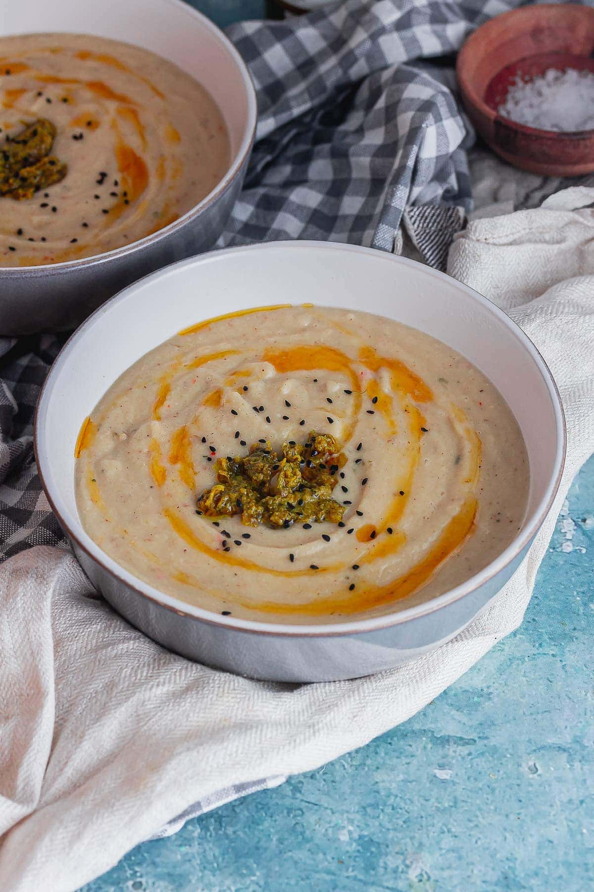 Grey bowl of creamy soup topped with chermoula