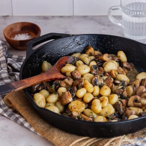 Black skillet of gnocchi with mushrooms on a marble background