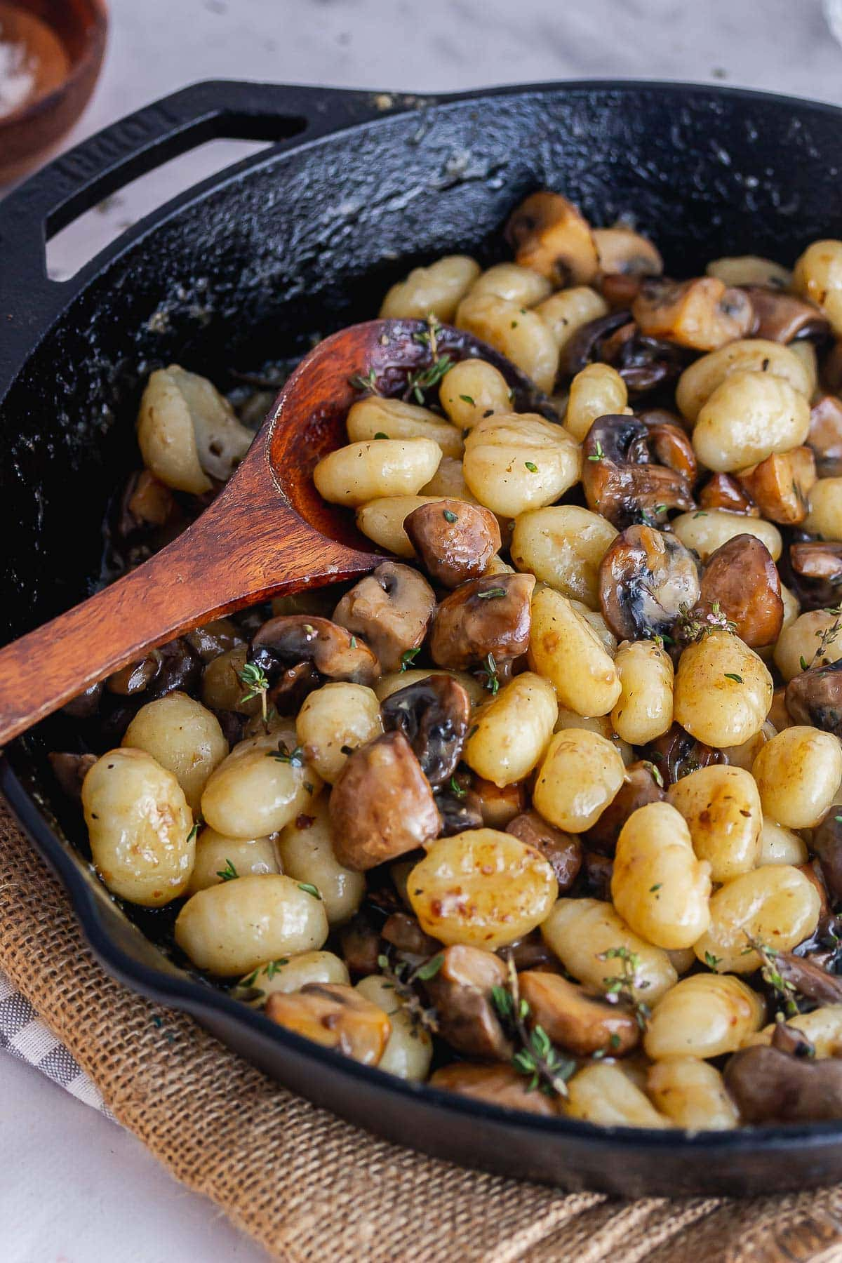 Gnocchi in a cast iron skillet with a wooden spoon on a hessian mat