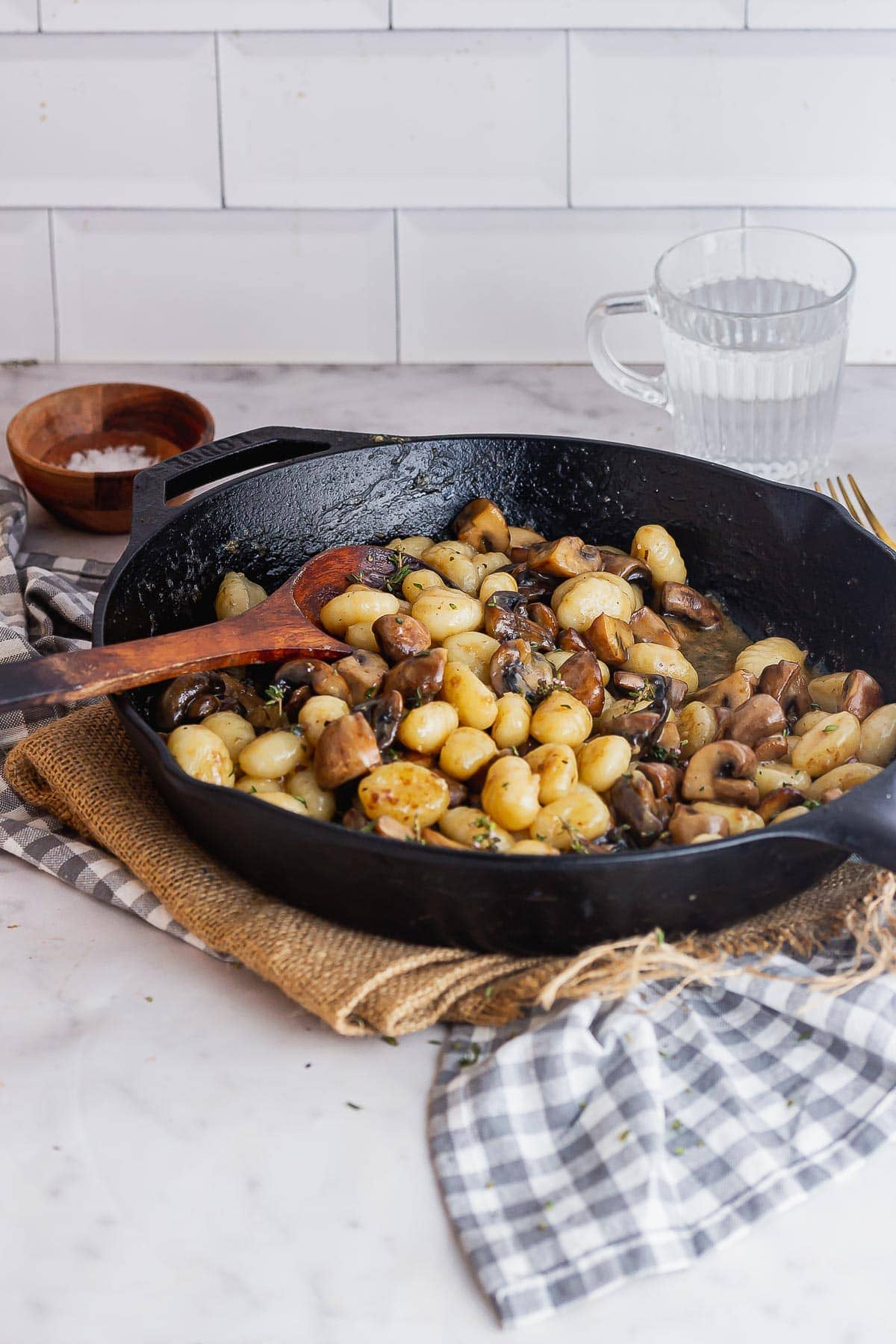 Black skillet of buttery gnocchi on a checked cloth