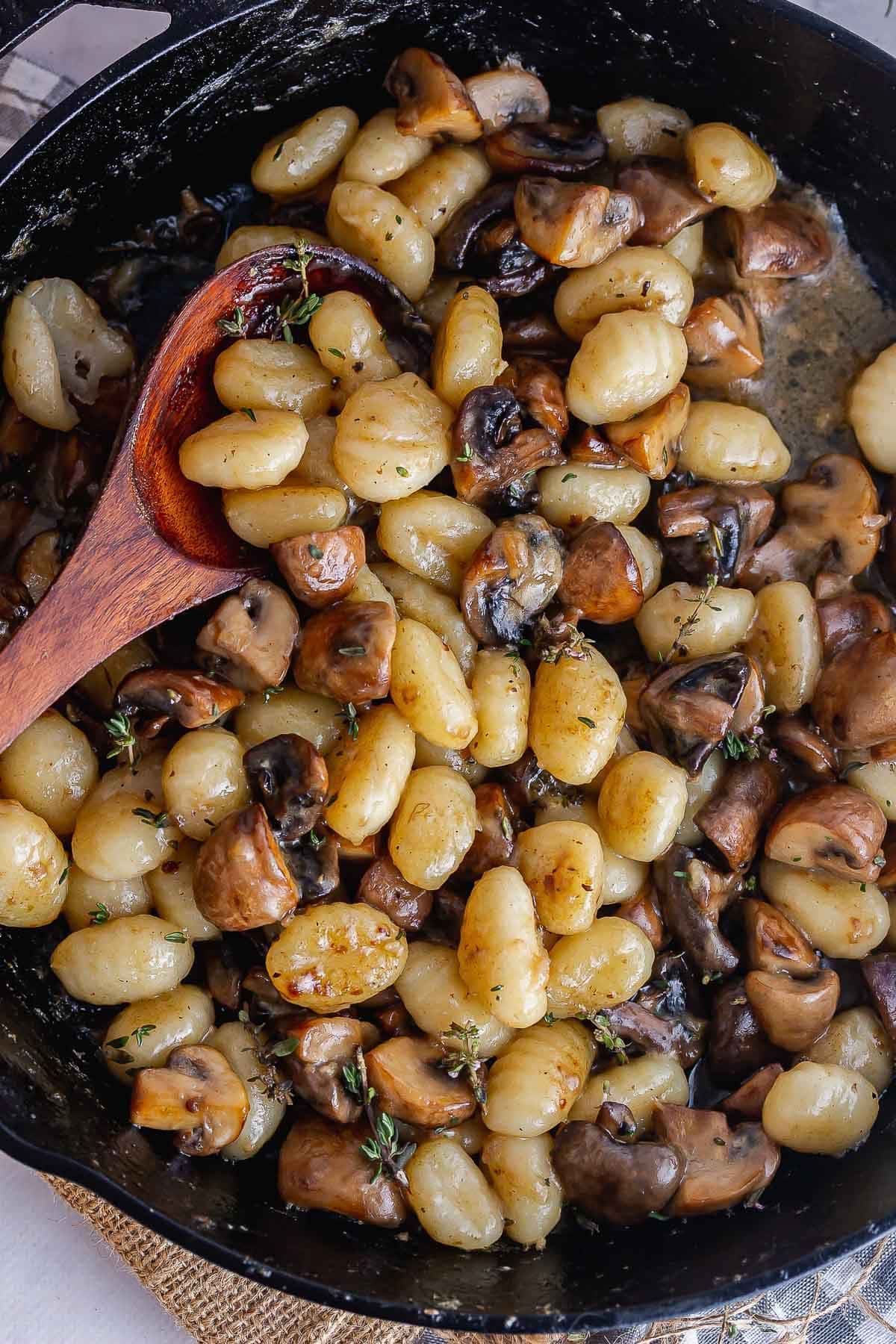 Overhead shot of mushroom gnocchi with a wooden spoon