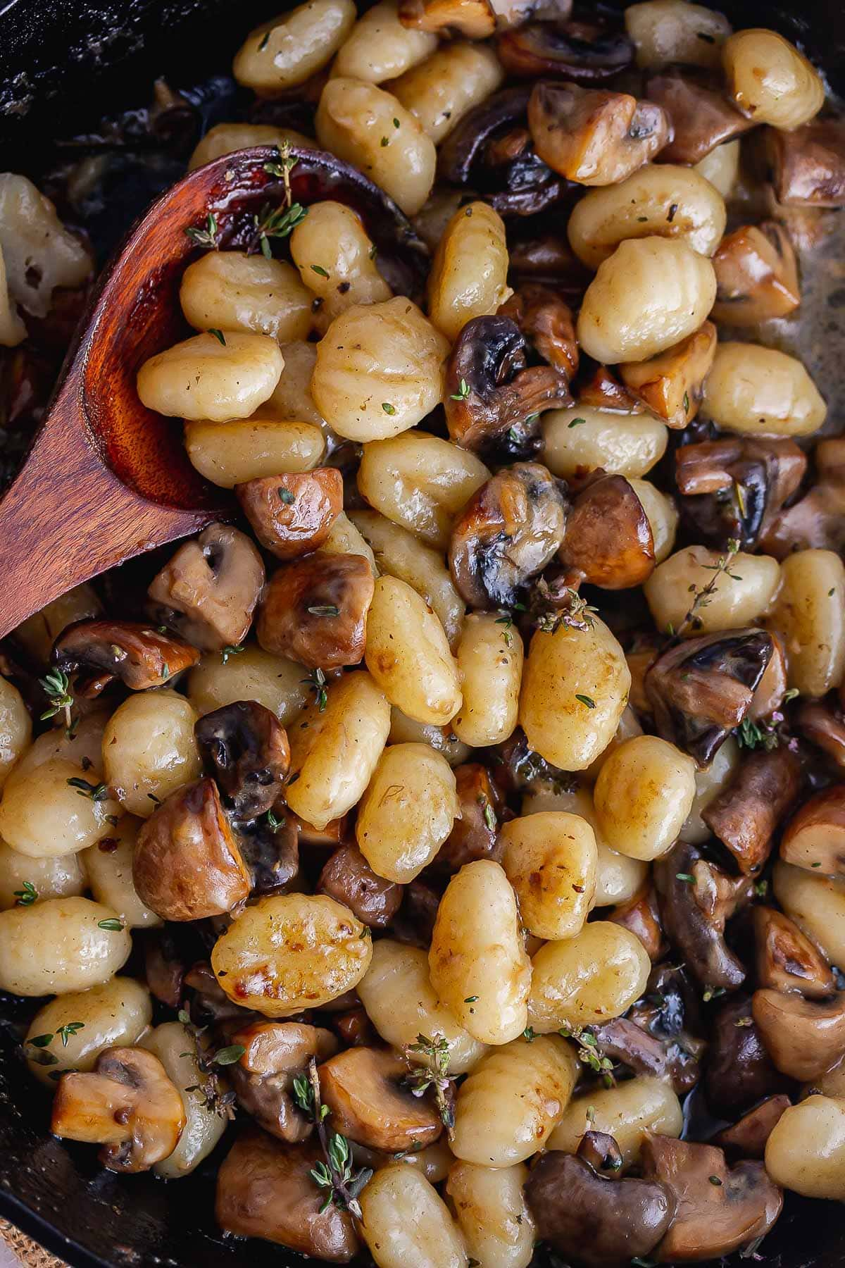 Overhead shot of gnocchi and mushrooms with a wooden spoon