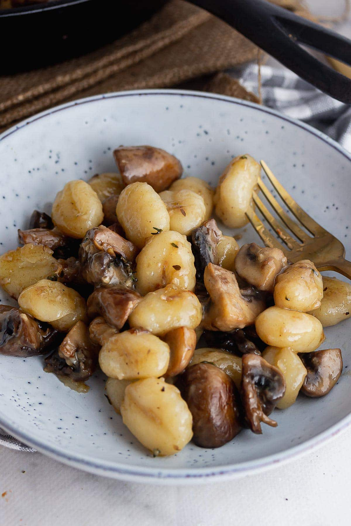 Blue bowl of mushroom and gnocchi with a gold fork