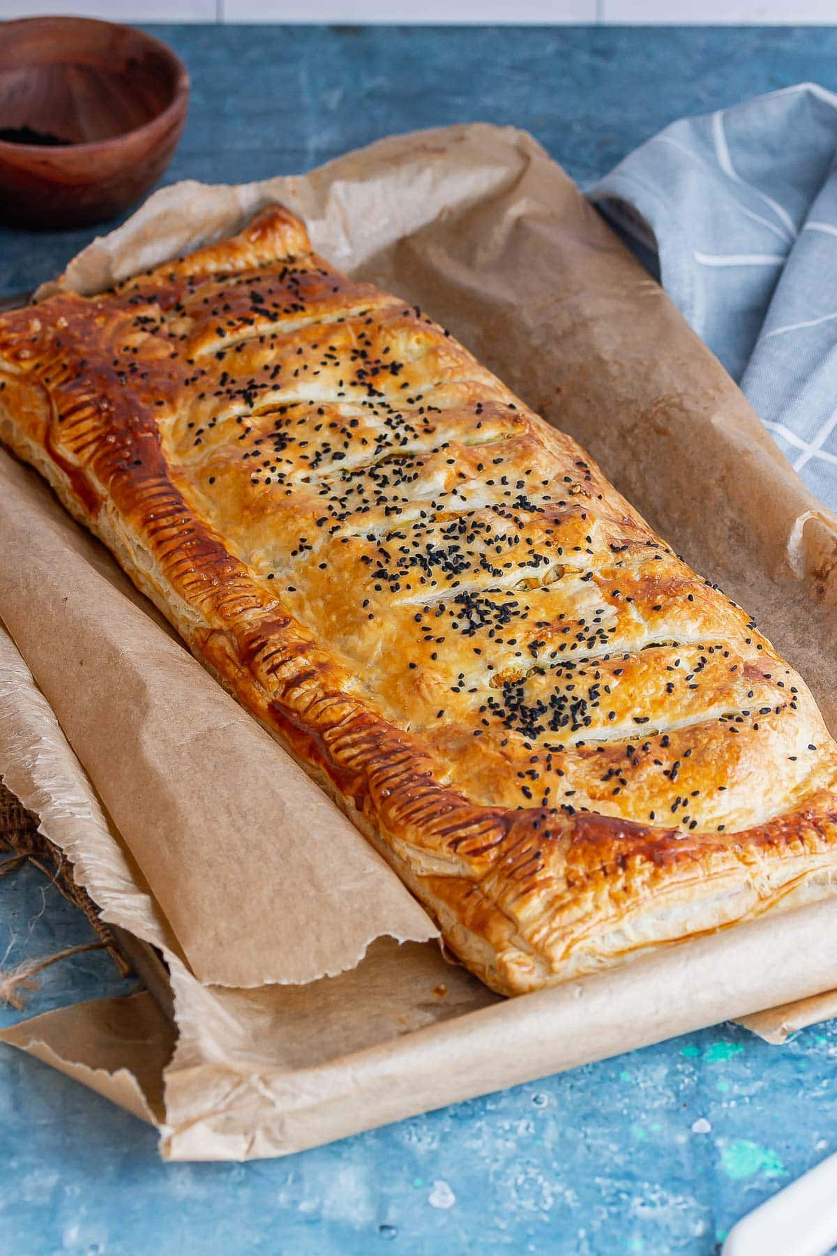 Butternut squash wellington on a baking sheet on a blue background
