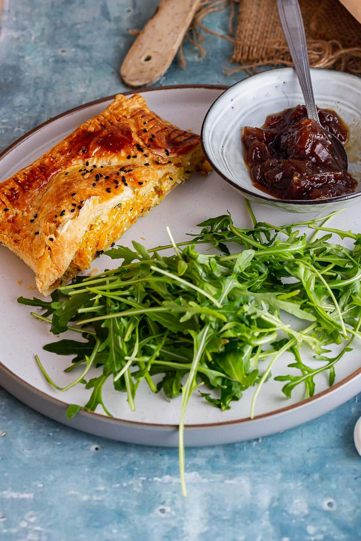 Grey plate with veggie wellington and salad on a blue background