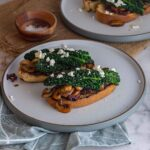 Grey plate of toasts topped with mushrooms and cavolo nero on a blue cloth