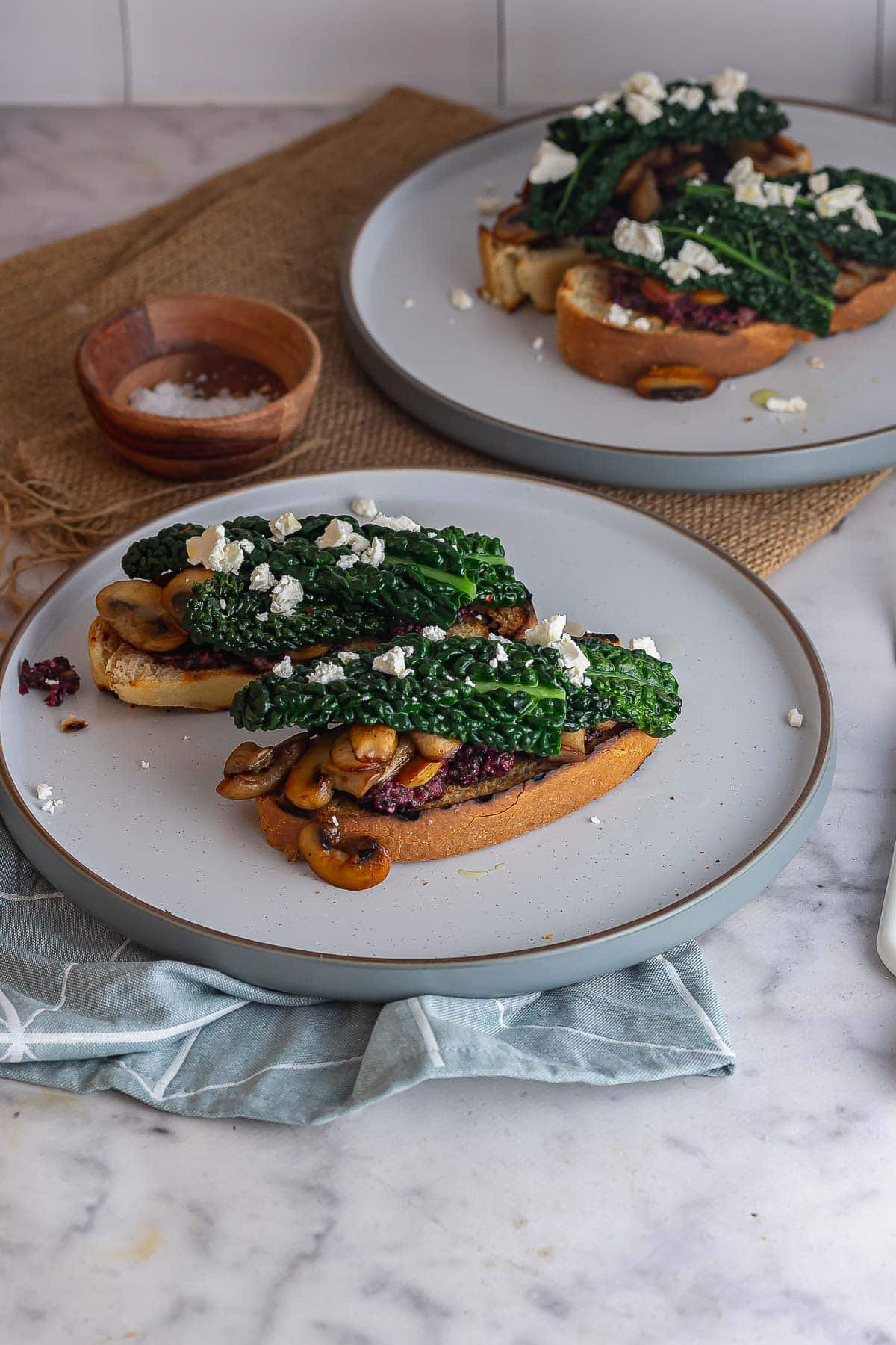 Grey plates of mushroom and cavolo nero toasts on a marble background