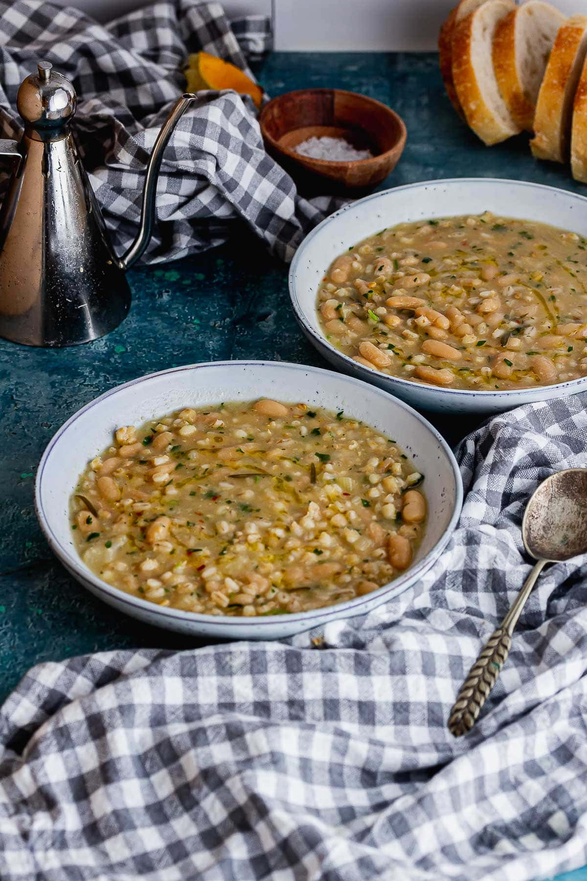 Bean and pearl barley soup on a blue surface with a tea towel