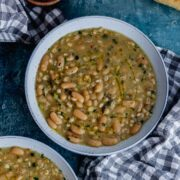 Overhead shot of bean and barley soup on a blue background