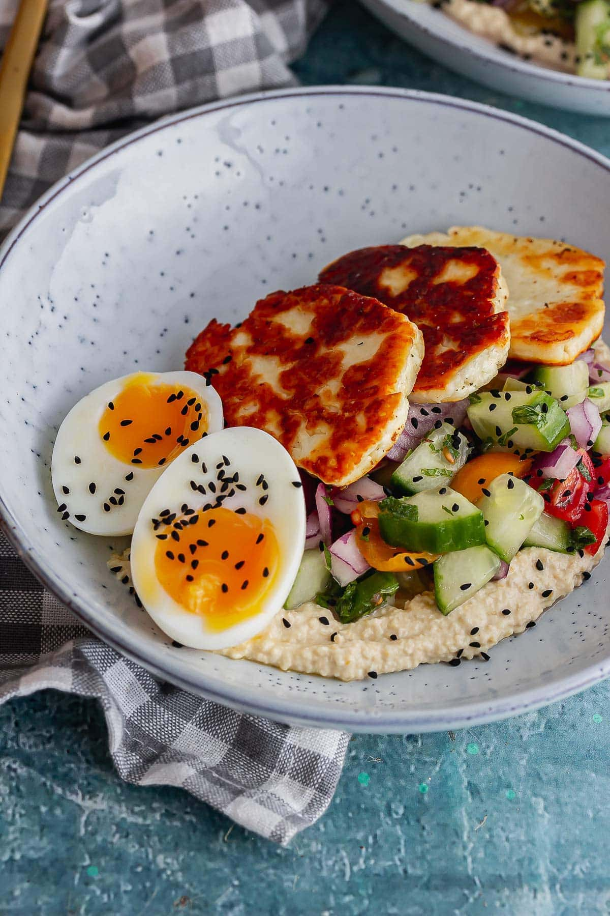 Close up of a runny boiled egg and halloumi in a blue bowl