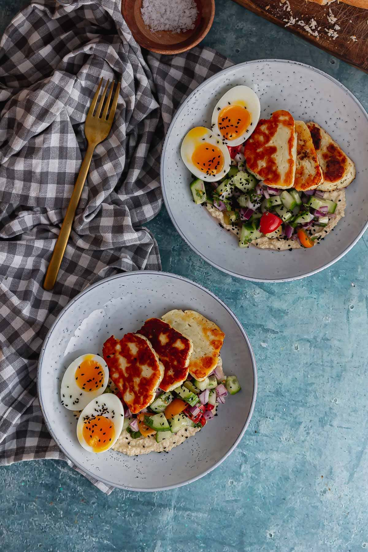 Overhead shot of halloumi breakfast bowls on a blue background