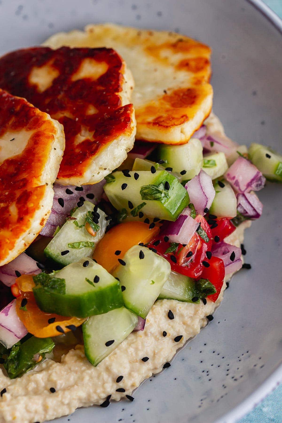 Close up of halloumi and salad on hummus