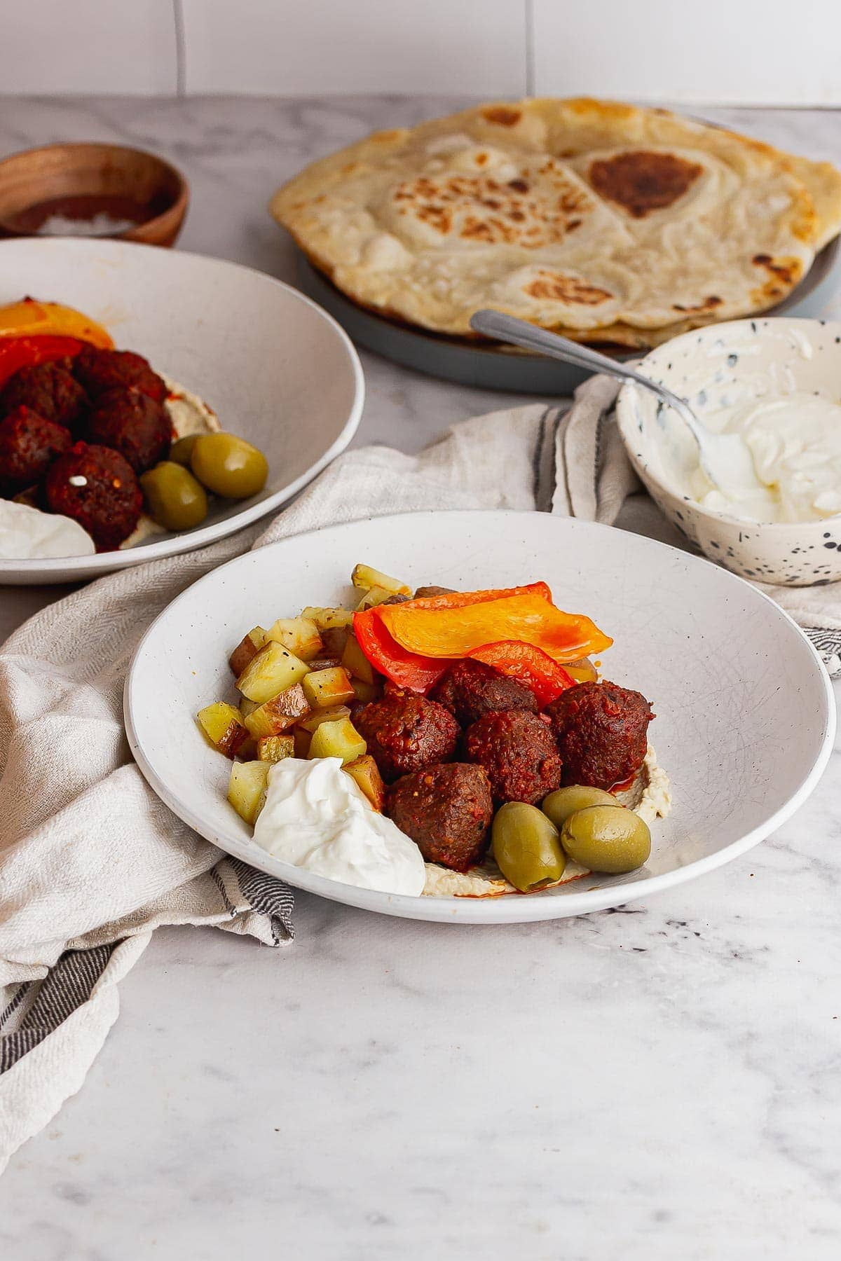 Bowls and meatballs and feta sauce on a marble background