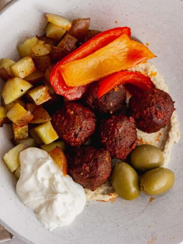 Meatballs and potatoes on a bed of hummus