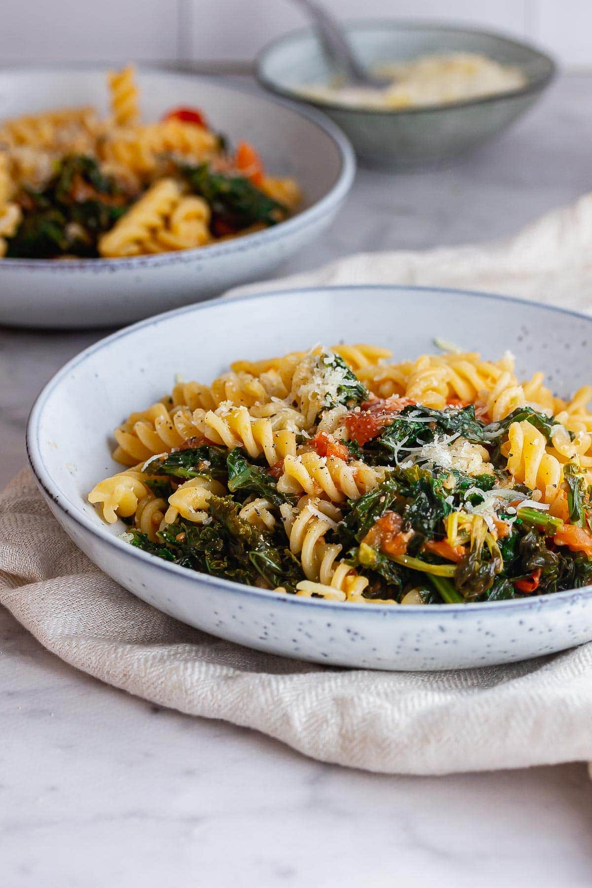 Side shot of pasta with kale and tomatoes on a marble surface