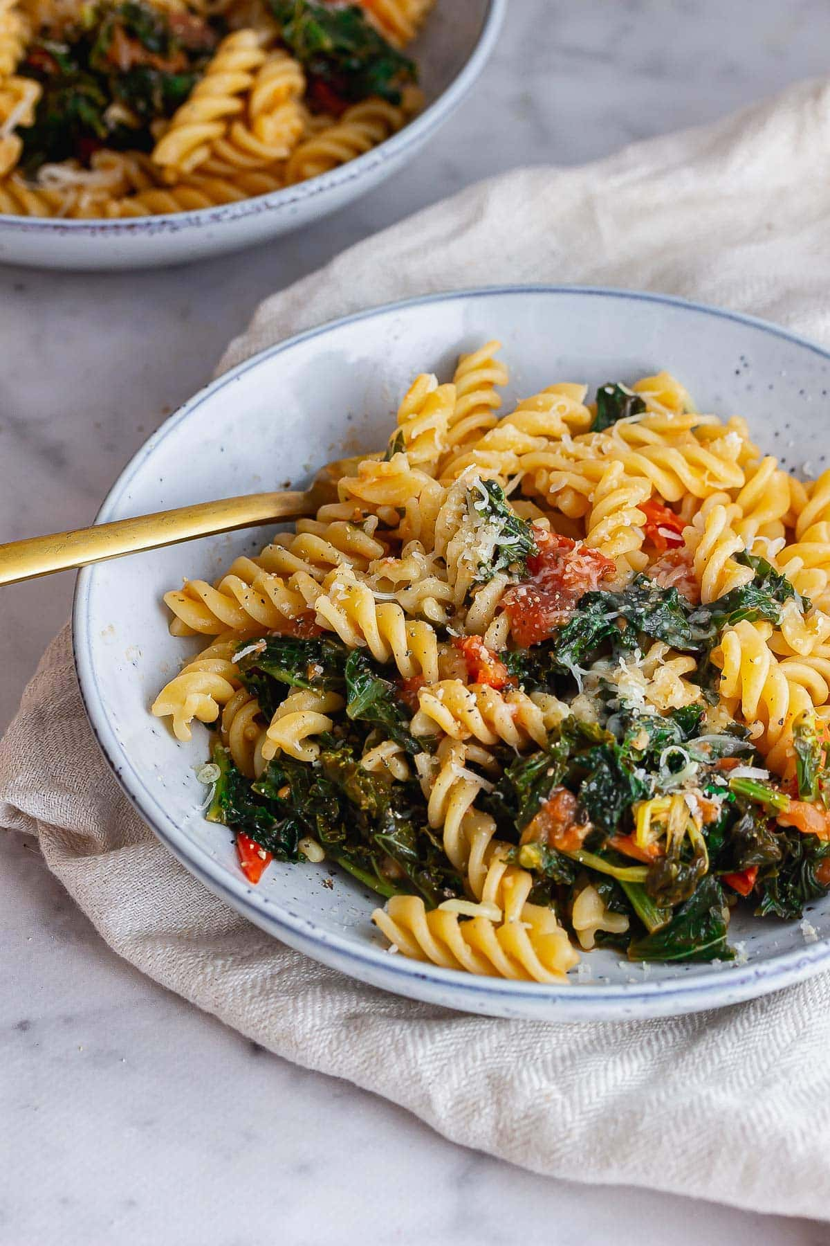 Blue bowl of cherry tomato pasta with a gold fork