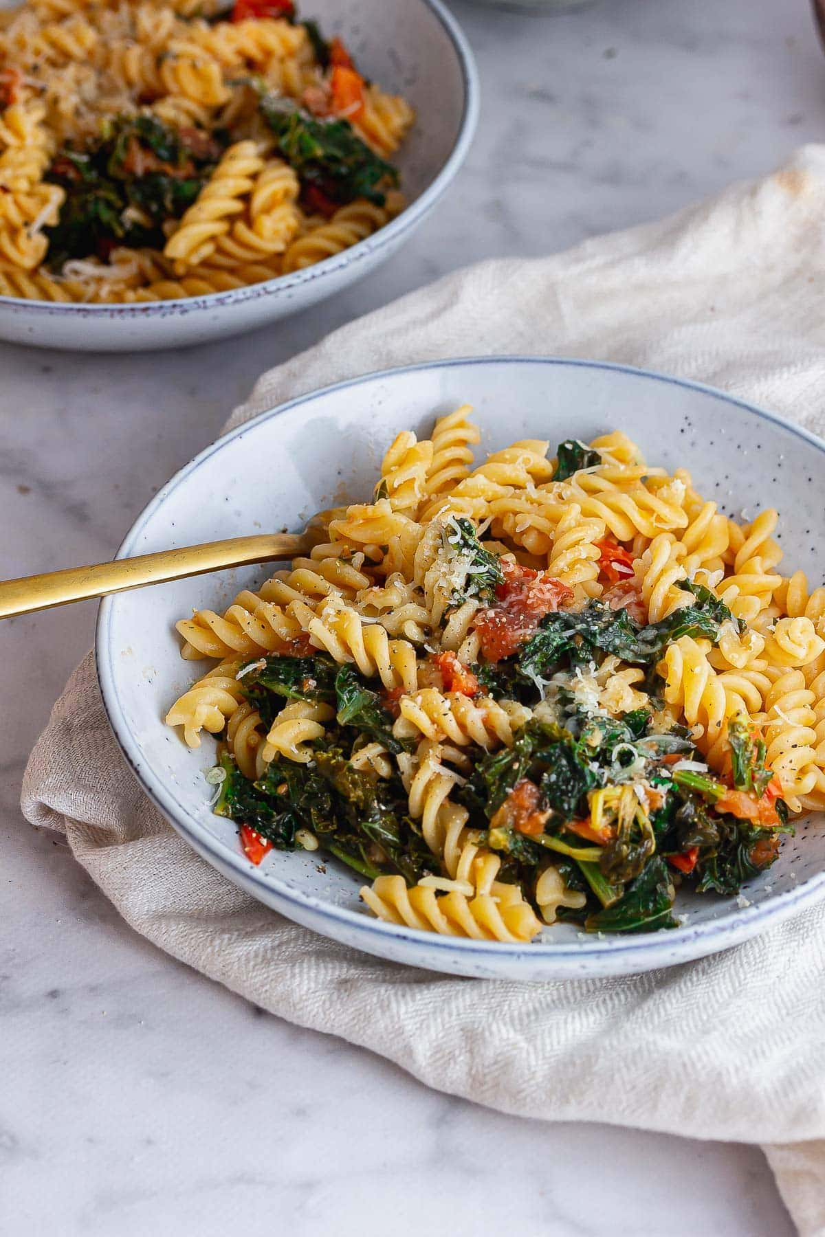 Blue bowl of tomato kale pasta on a marble background