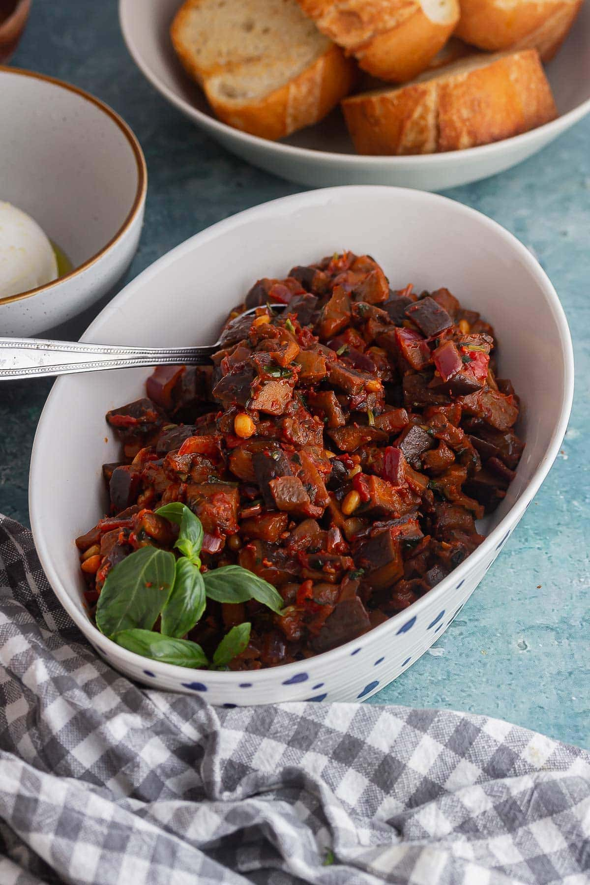 White dish of caponata on a blue background
