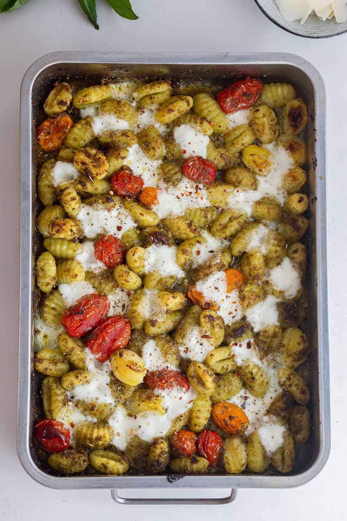 Overhead shot of baking sheet gnocchi on a white background