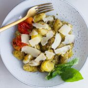 Overhead shot of blue bowl of gnocchi on a white background
